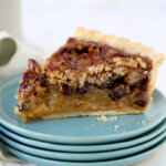 a slice of pecan tart sitting on four dishes