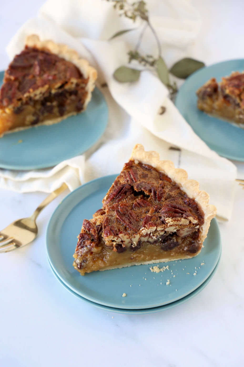 three slices of pecan tart on turquoises dishes