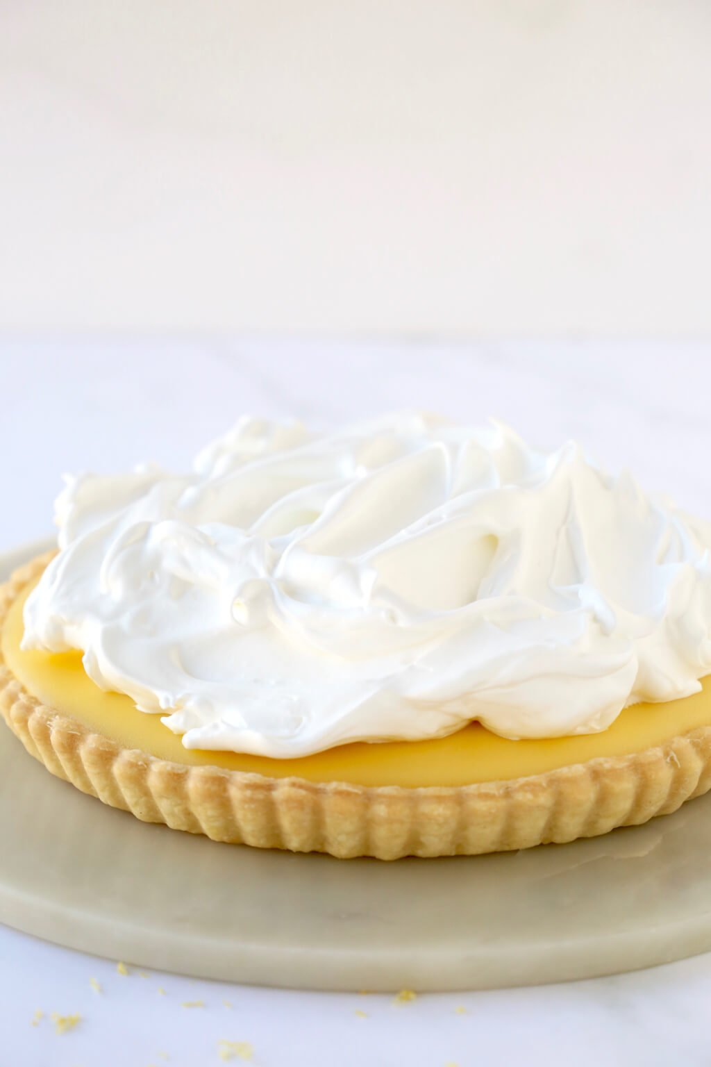 tart shell filling with lemon curd and topped with a pile of meringue