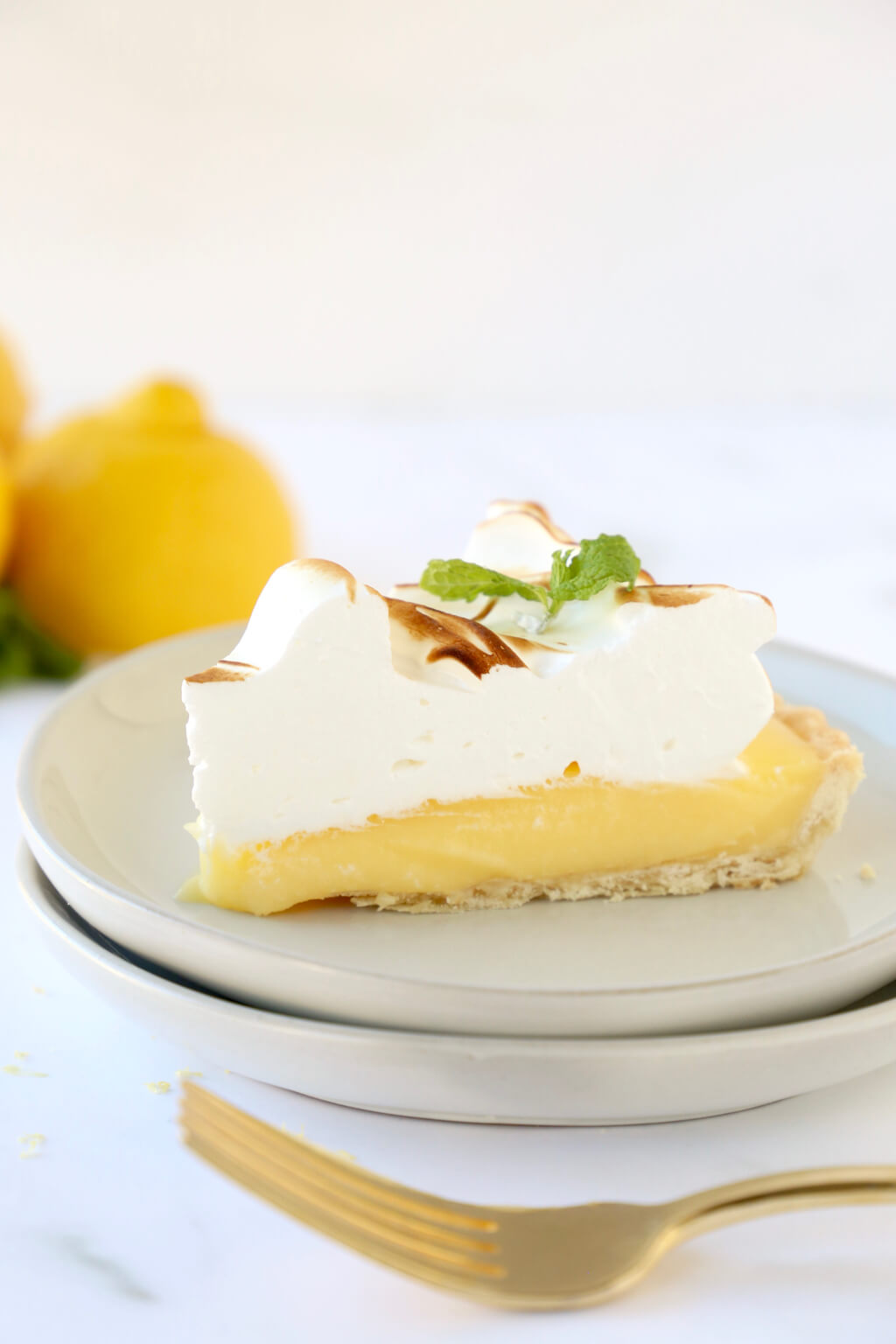 a close up of a slice of lemon meringue tart