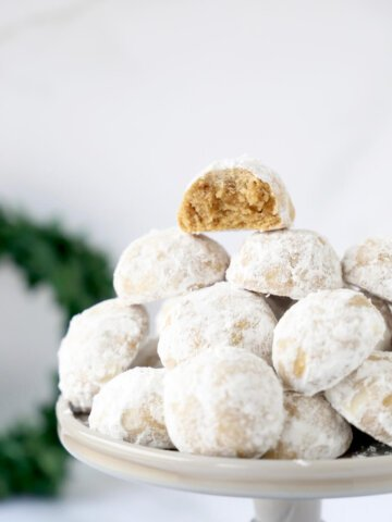 a close up shop of gingerbread snowball cookies one with a bite taken out