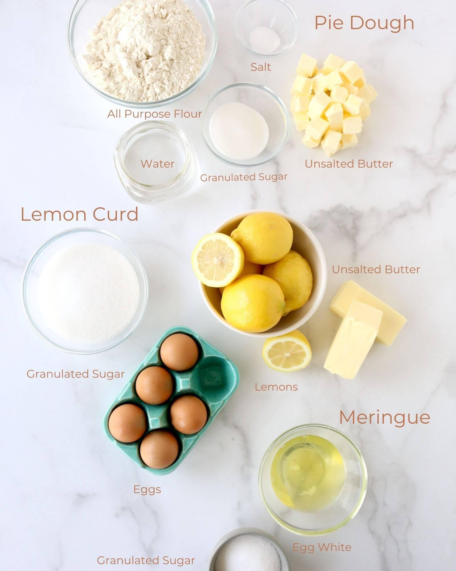 bowls of flour, sugar, salt, butter, lemons, eggs, and egg whites.