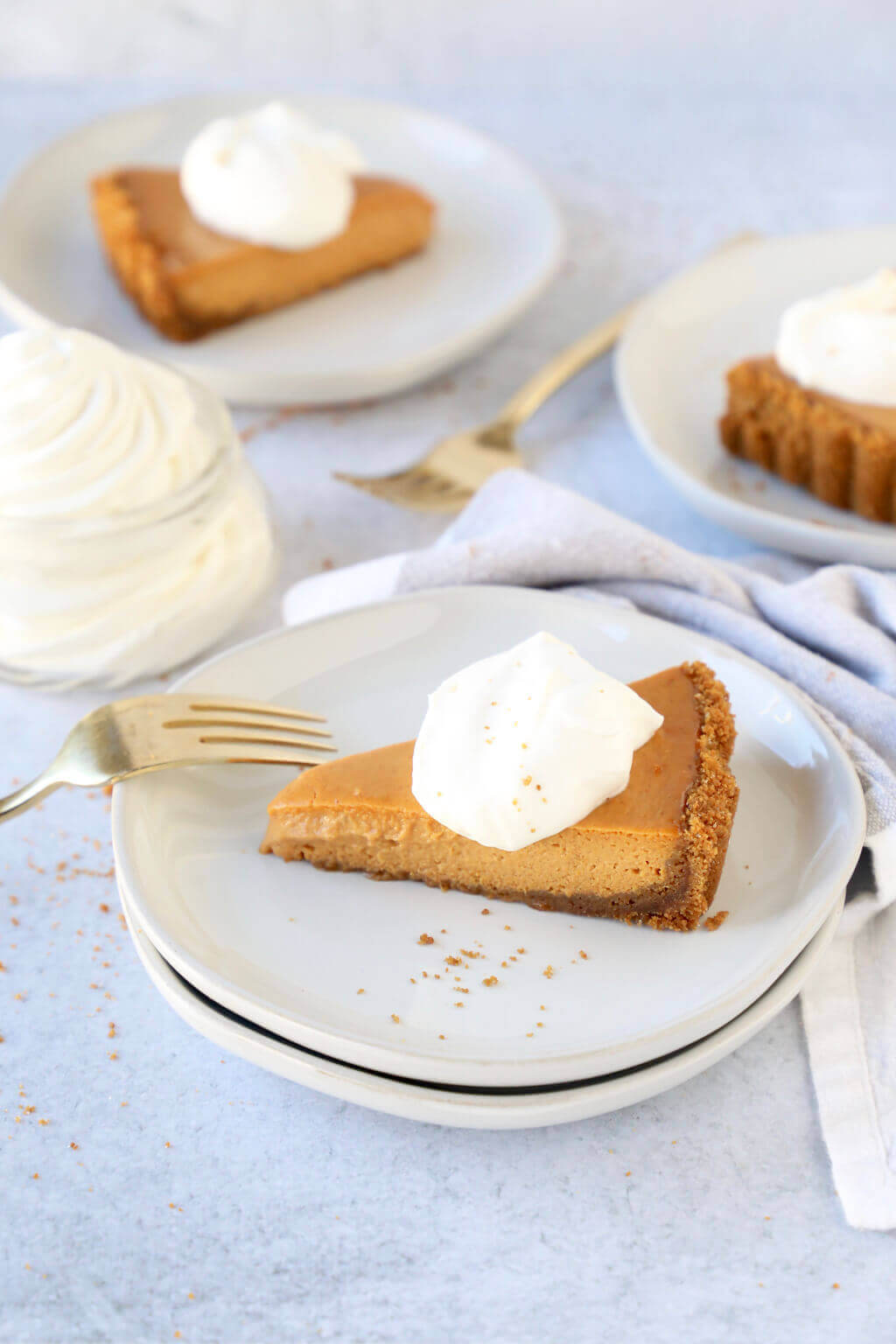 A slice of pumpkin gingersnap tart topped with whipped cream, with a few more slices sitting in the background