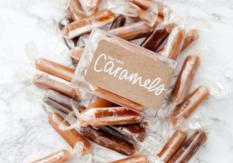 A box of sea salt caramel candy with caramels surrounding the box