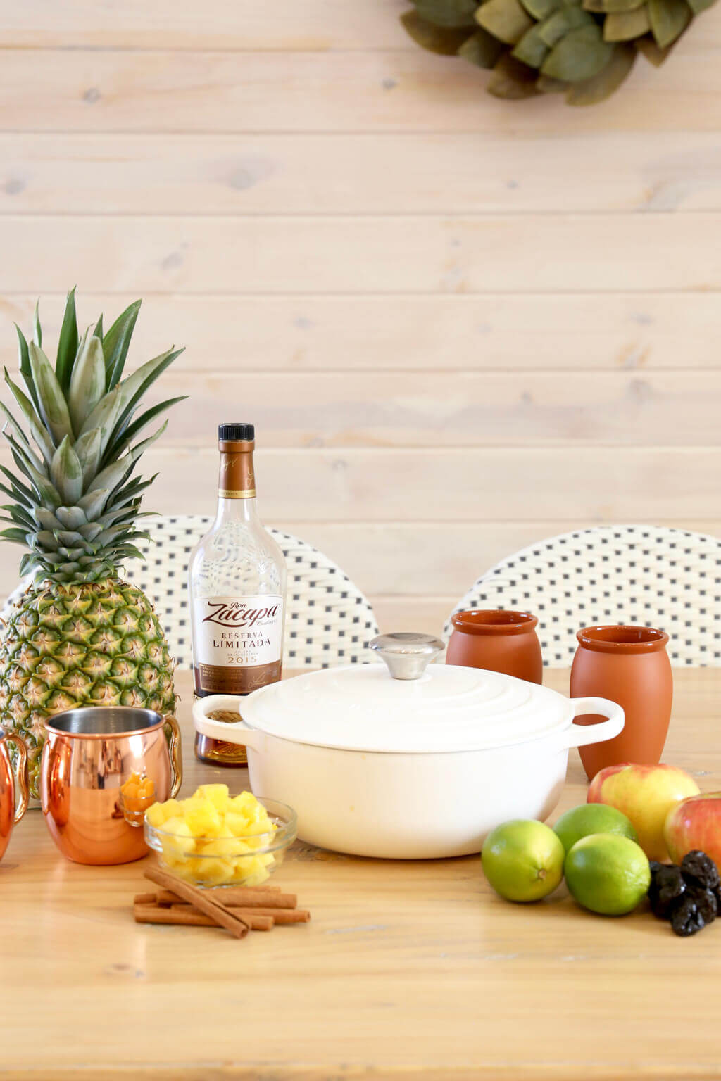 a pot, chopped pineapple, limes, apples, prunes, rum and copper mugs