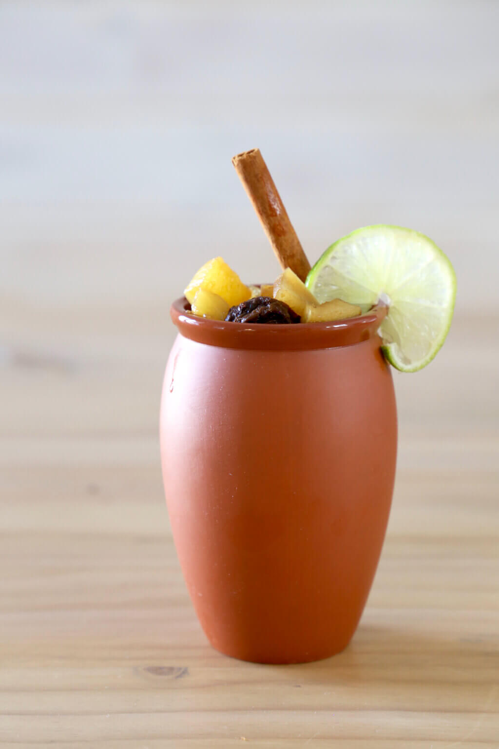 one clay mug filled with christmas punch and a cinnamon stick