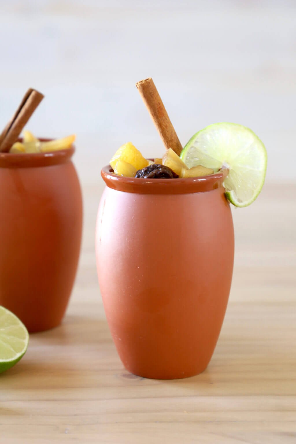 two clay mugs filled with christmas punch and a cinnamon stick