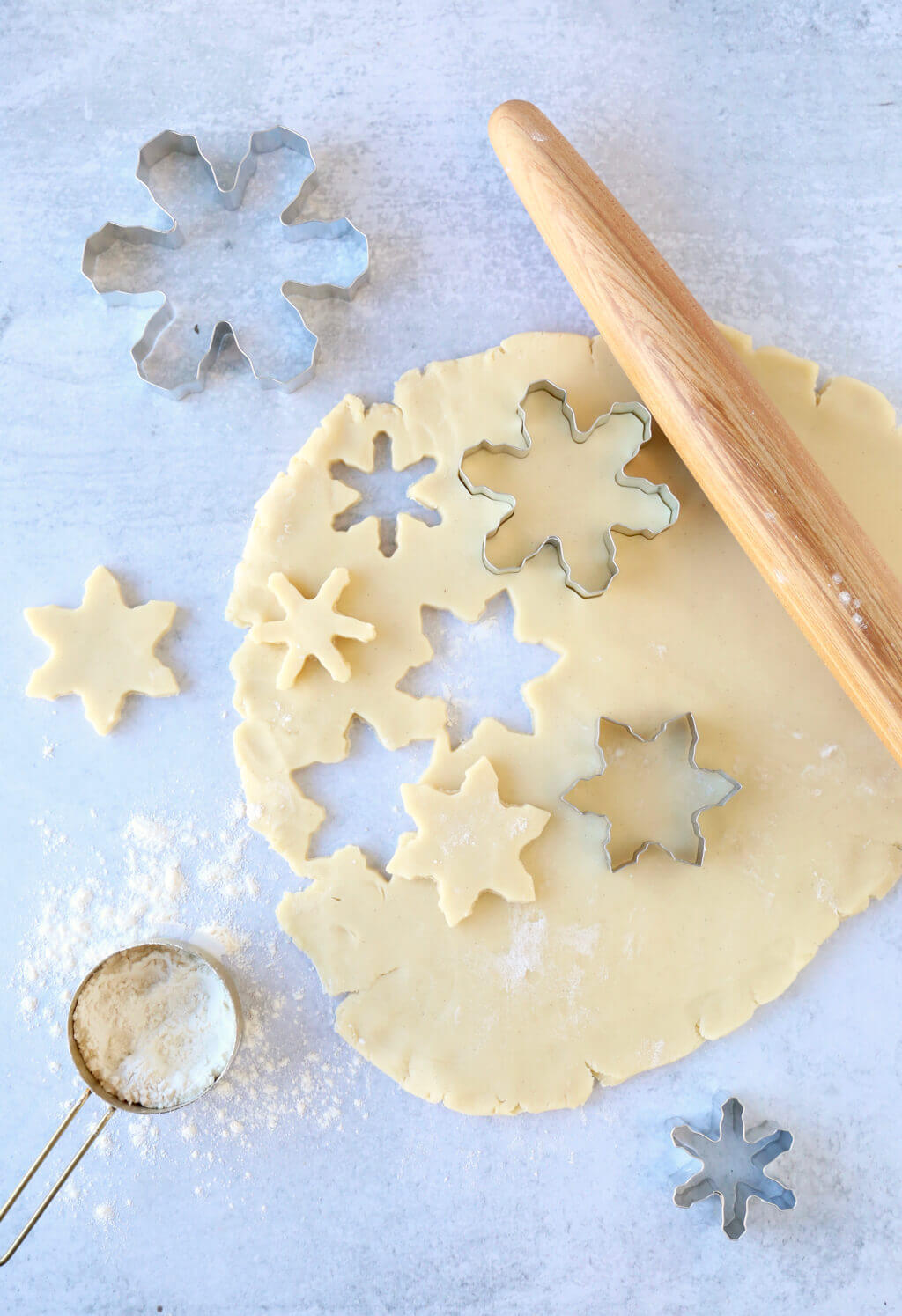 dough rolled out with a rolling pin and snowflake cookie cutters cutting the dough