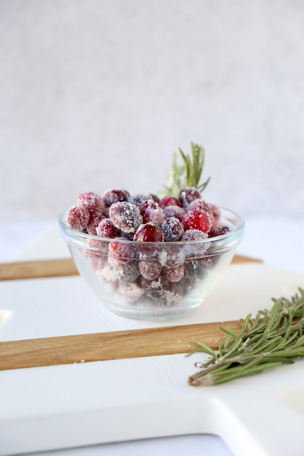 a bowl full of sugared cranberries and a sprig of rosemary