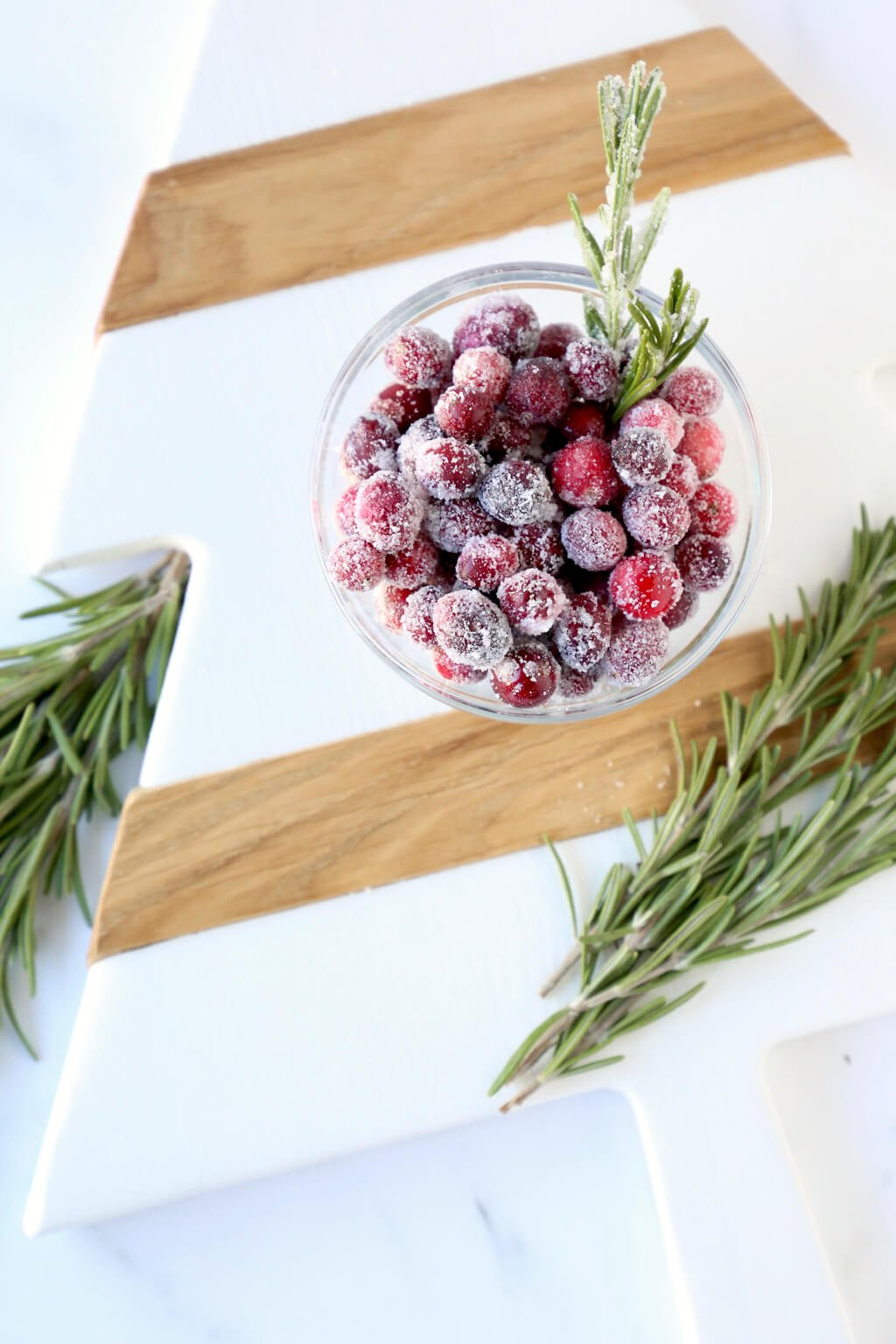 an overhead view of a bowl of sugared cranberries surrounded by rosemary sprigs