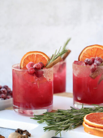 three glasses of a christmas cocktail with rosemary, cinnamon and dried grapefruit