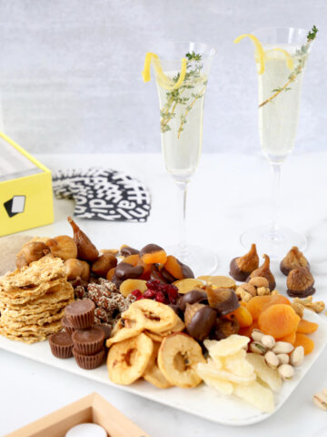 two glasses of champagne with a snack board of dried fruits and nuts and games in the background