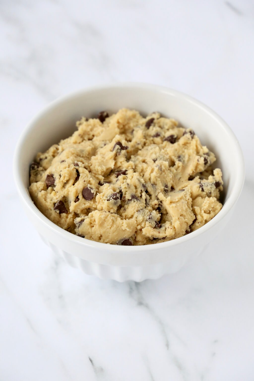 a white bowl filled with chocolate chip cookie dough