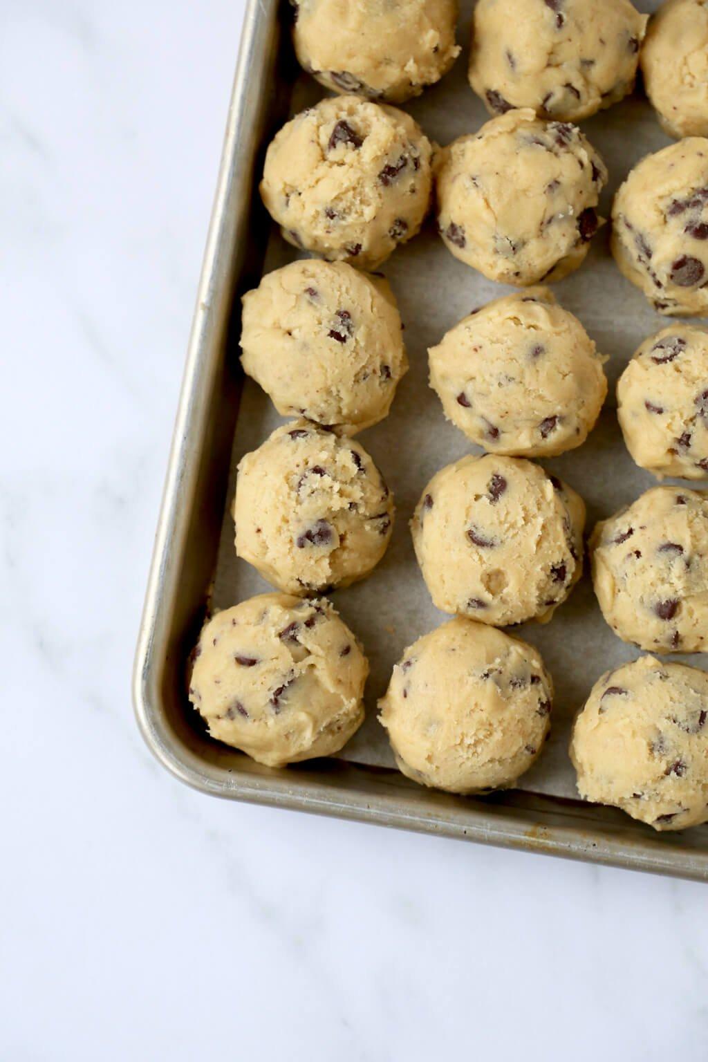 raw cookie dough balls on a baking sheet