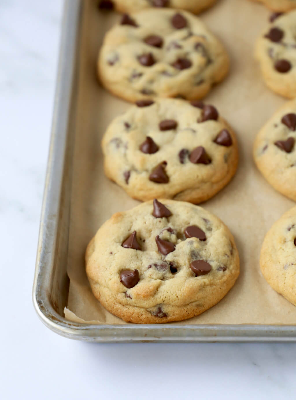 a sheet pan lined with chocolate chip cookies fresh out of the oven