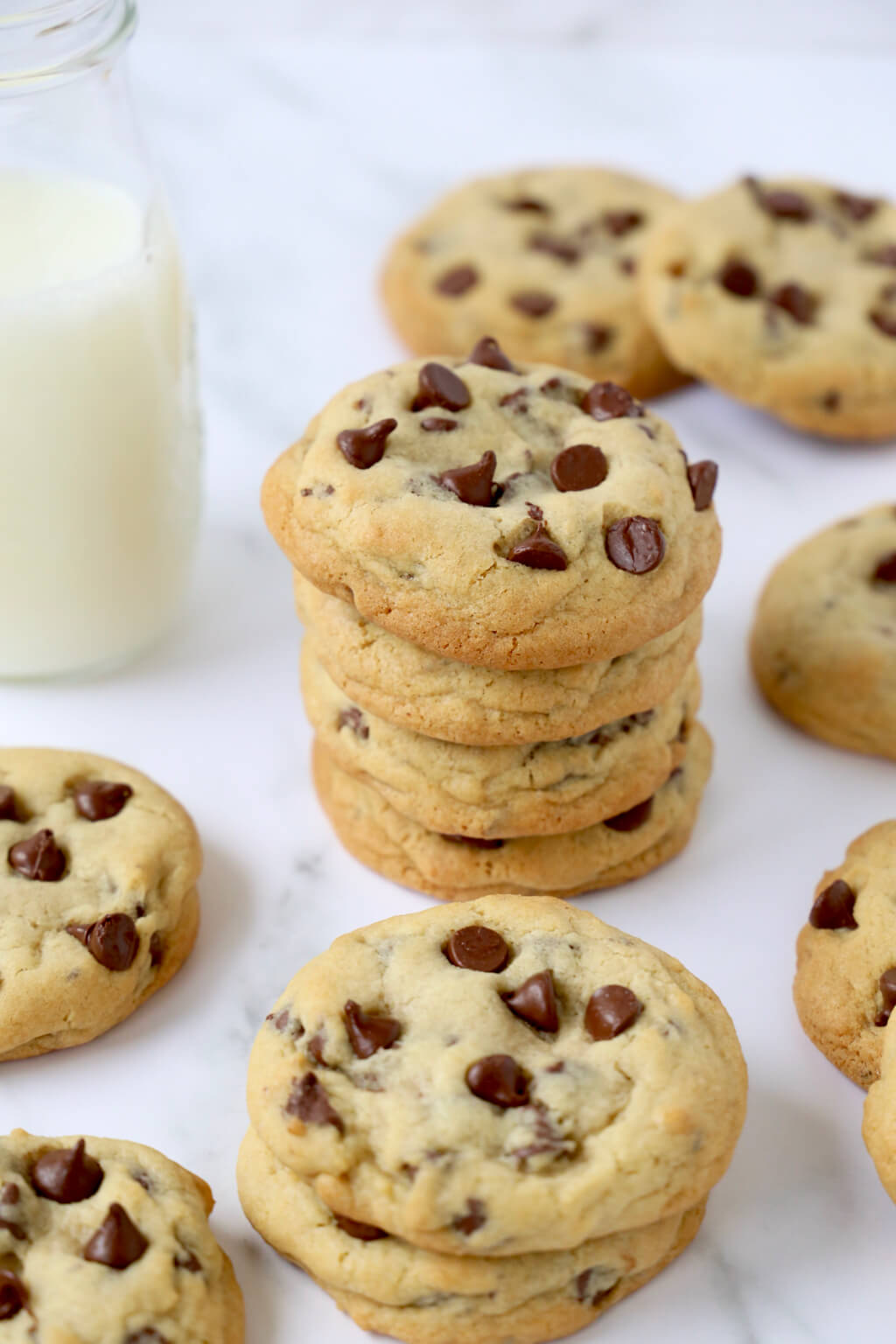 a stack of chocolate chip cookies surround by more chocolate chip cookies