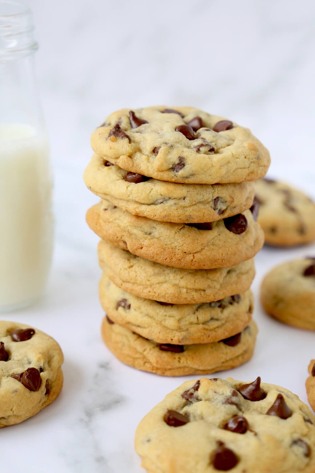 a stack of six chocolate chip cookies in front of a glass of milk