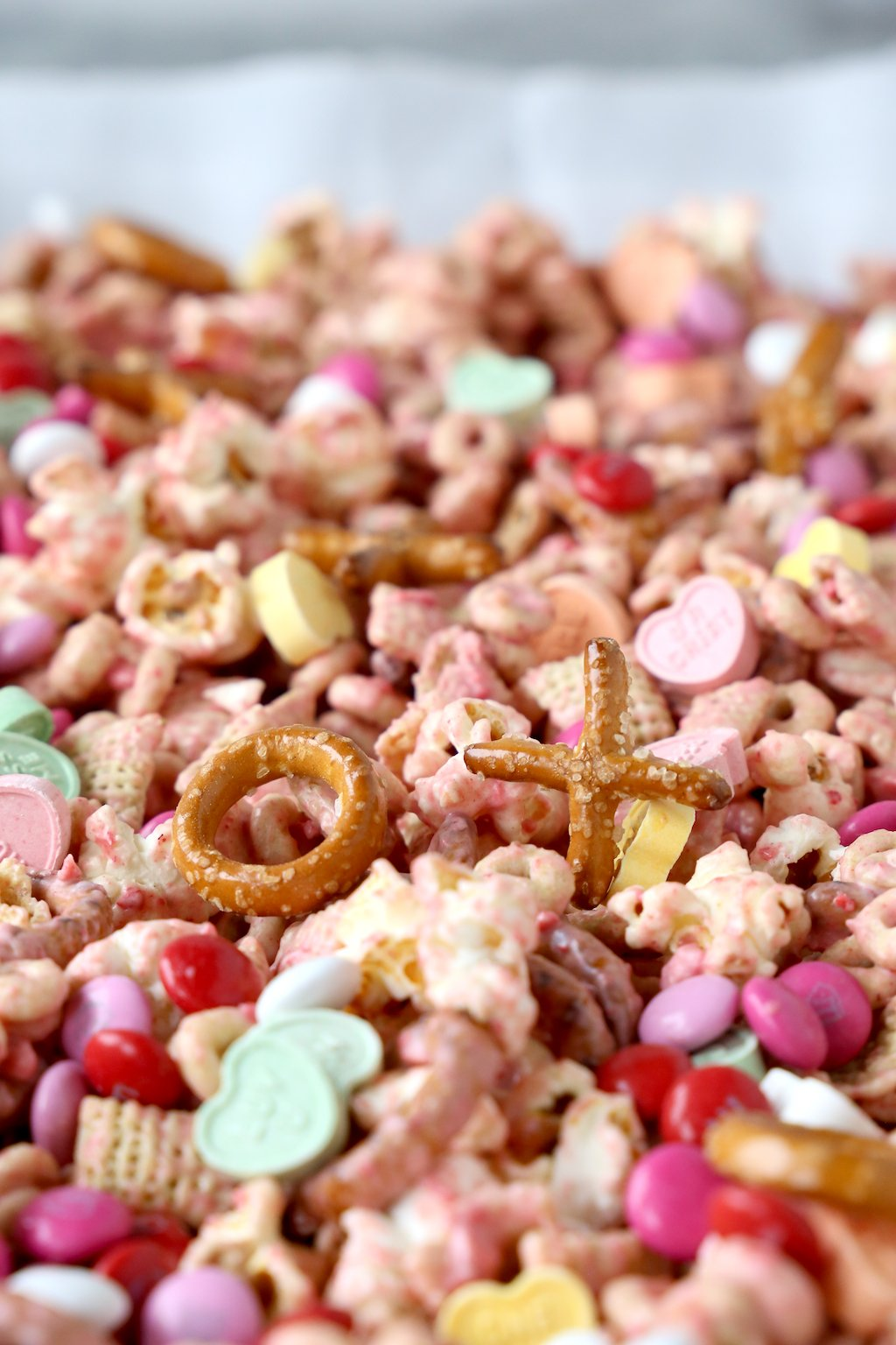 a sheet pan of snack mix made of chex, cheerios, popcorn, pretzels, m&m's and conversation hearts
