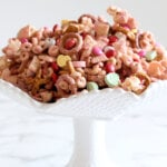 a bowl of snack mix with pretzels, chex mix, popcorn, cheerios and m&m's