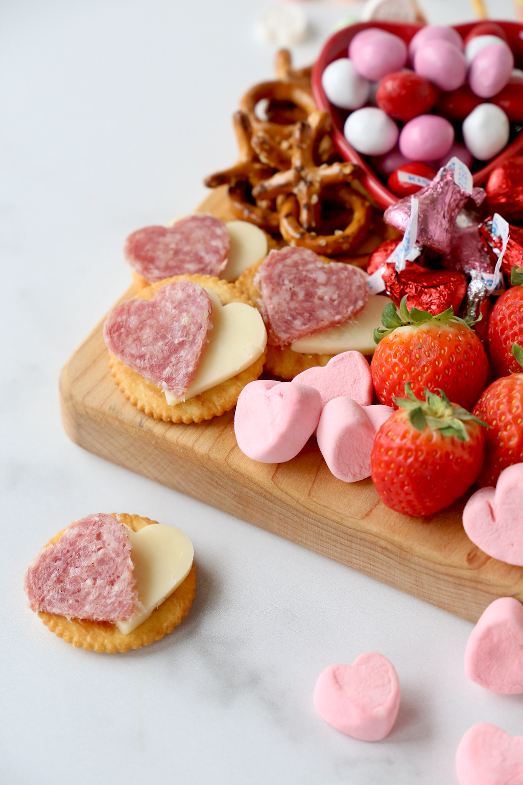 heart shaped salami and cheese on crackers placed on a valentine's snack board