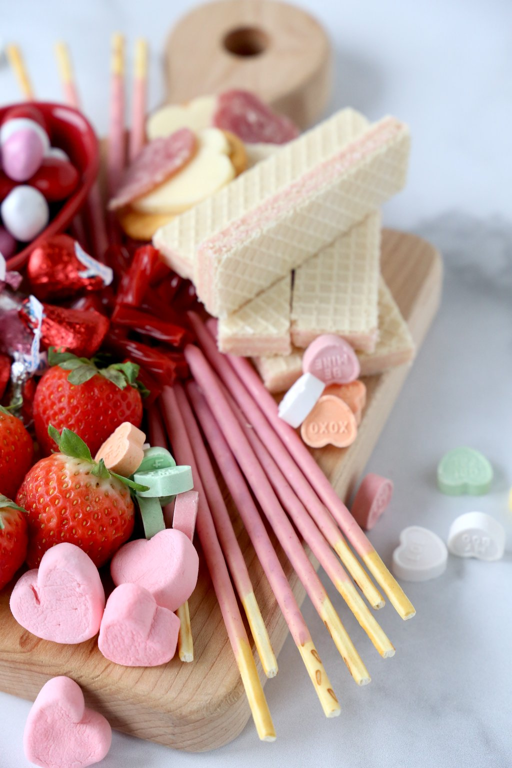 strawberry pokey sticks, strawberry wafer cookies, conversation hearts, chocolate and strawberries stacked on a wood board