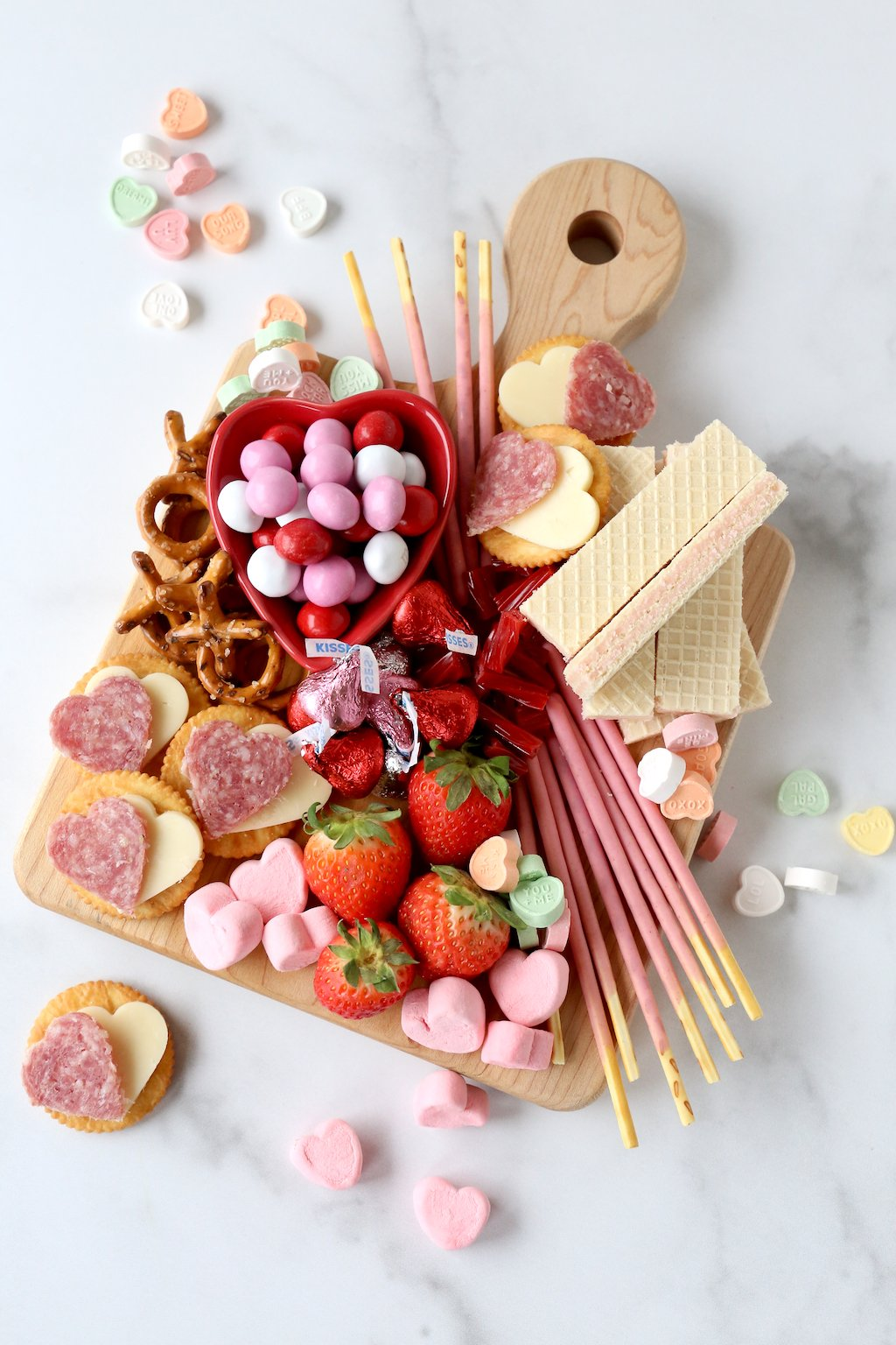 a wood cutting board filling with chocolate, marshmallows, strawberries, wafer cookies and salami and cheese crackers