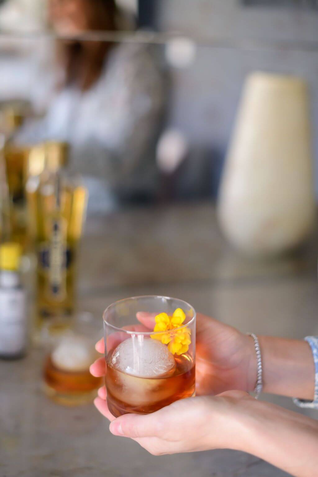 a women holding a clear glass with a big ice ball filled with elderflower, bourbon, bitters and an edible flower