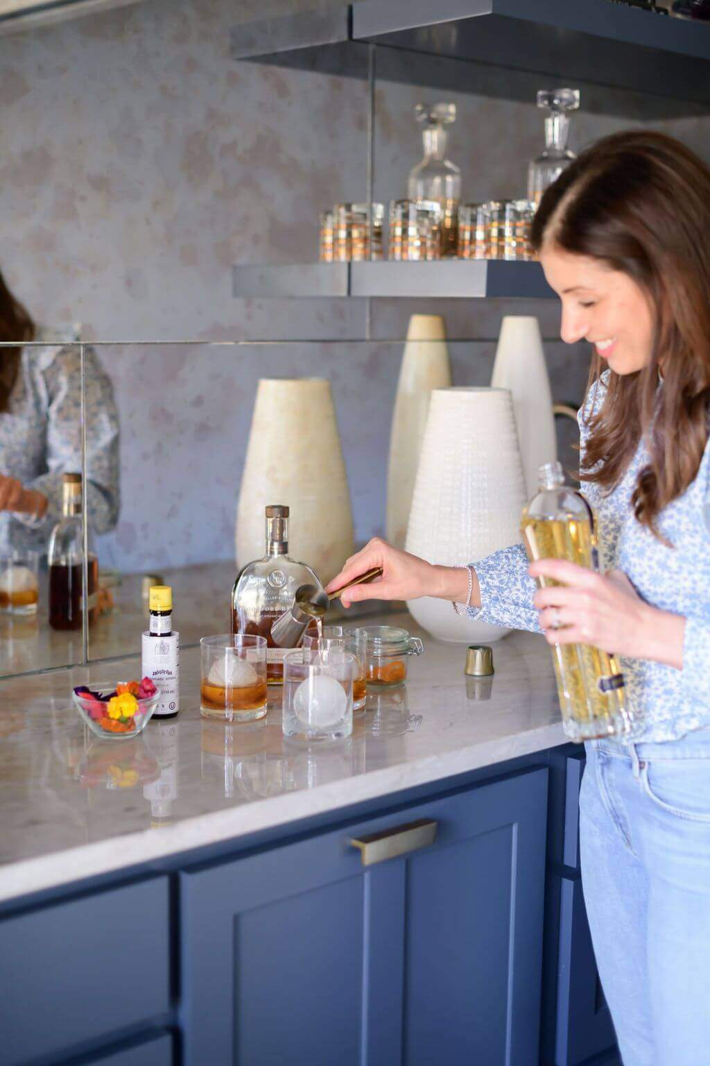 pouring a shot of st. germain liqueur into a glass ice