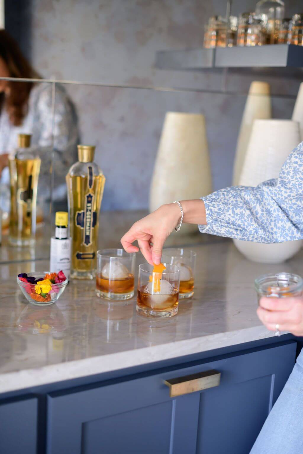 placing an orange peel in a glass filled with bourbon, bitters and elderflower