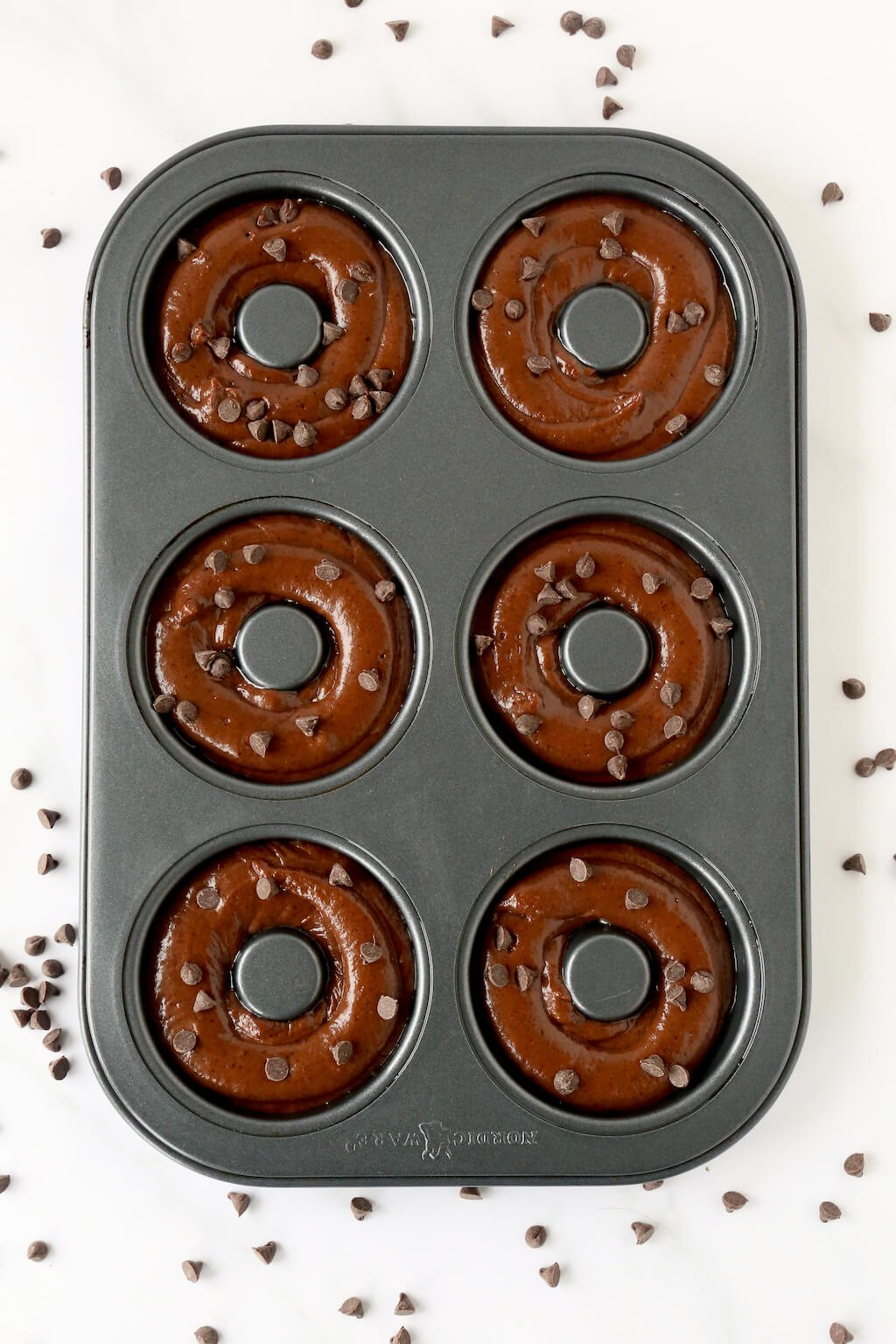 a pan of 6 unbaked donuts with chocolate chips sprinkled around