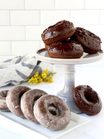 a cake stand stacked with chocolate donuts and a platter of glazed donuts next to it