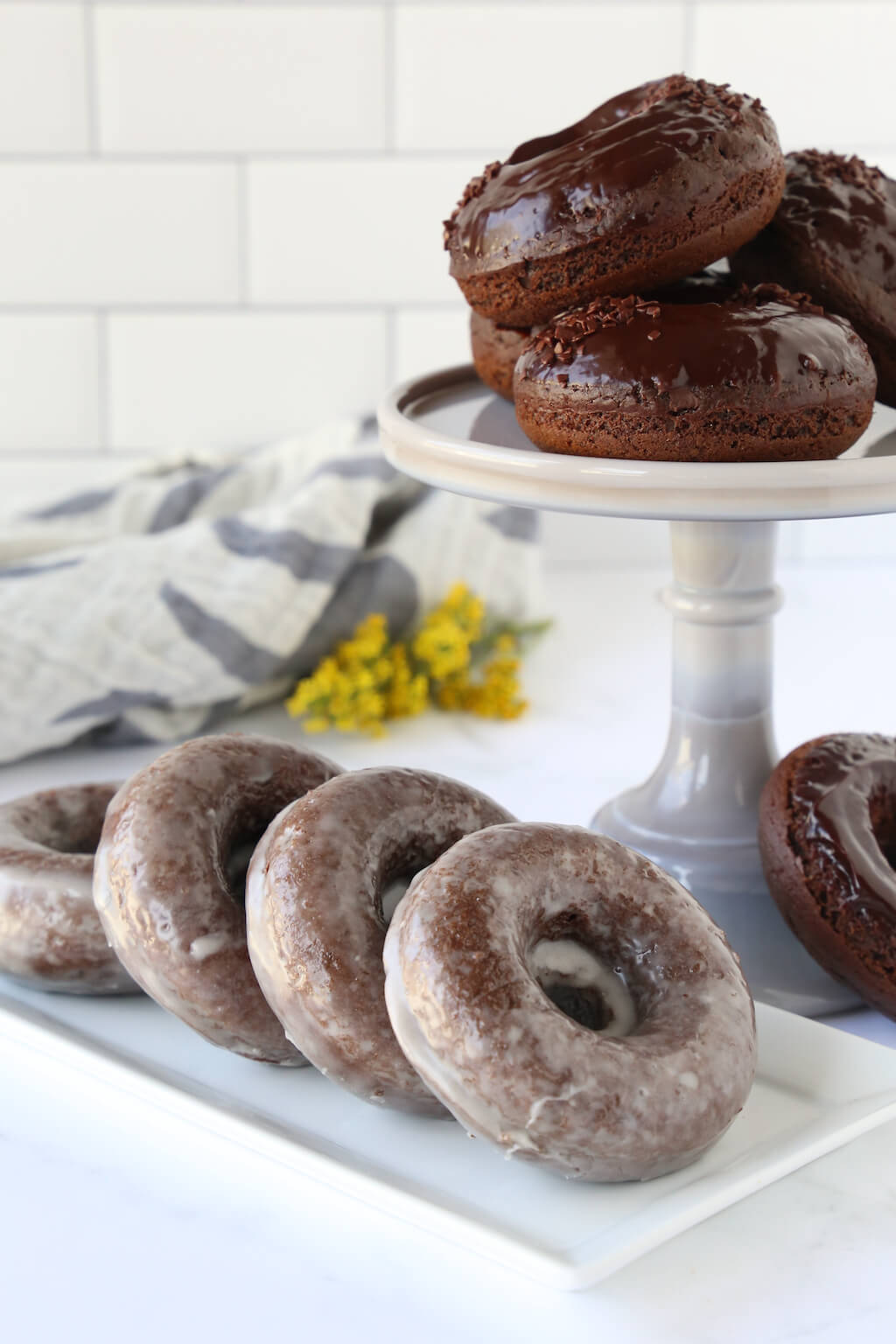 a cake stand stacked with chocolate glazed donuts and a platter of glazed chocolate donuts