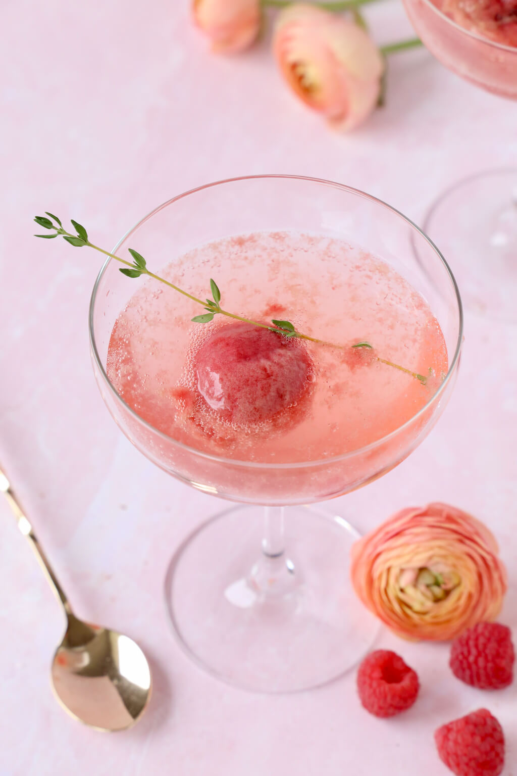 a glass of champagne with a scoop of raspberry sorbet and a sprig of thyme