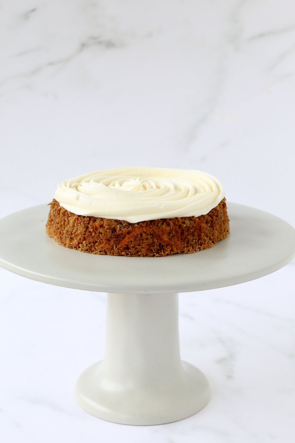 one layer of carrot cake with cream cheese frosting on a cake stand