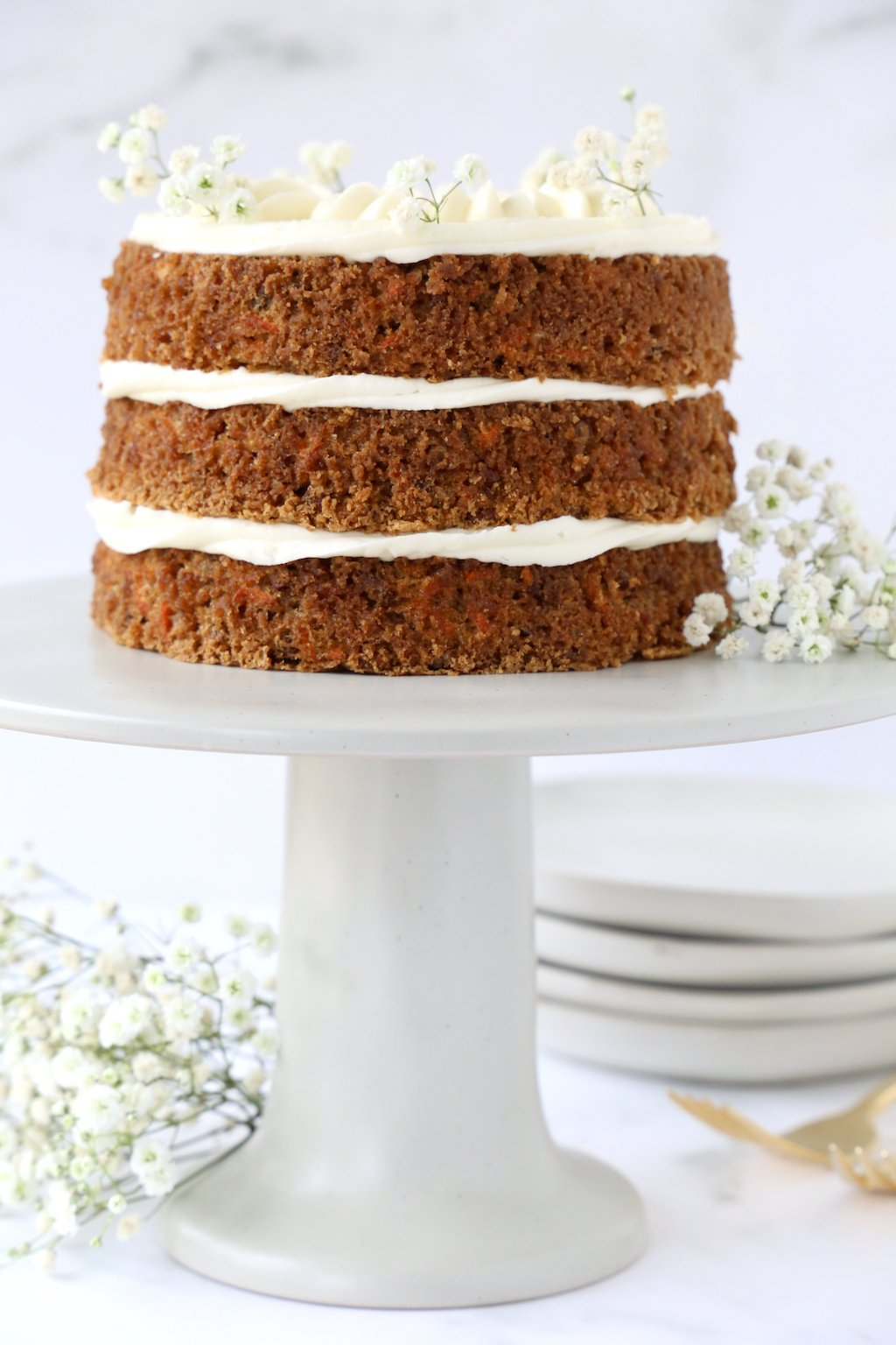three layers of carrot cake on a gray cake stand with babies breath garnishing the cake
