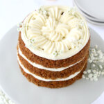three layers of carrot cake with cream cheese frosting on a gray cake cakestand