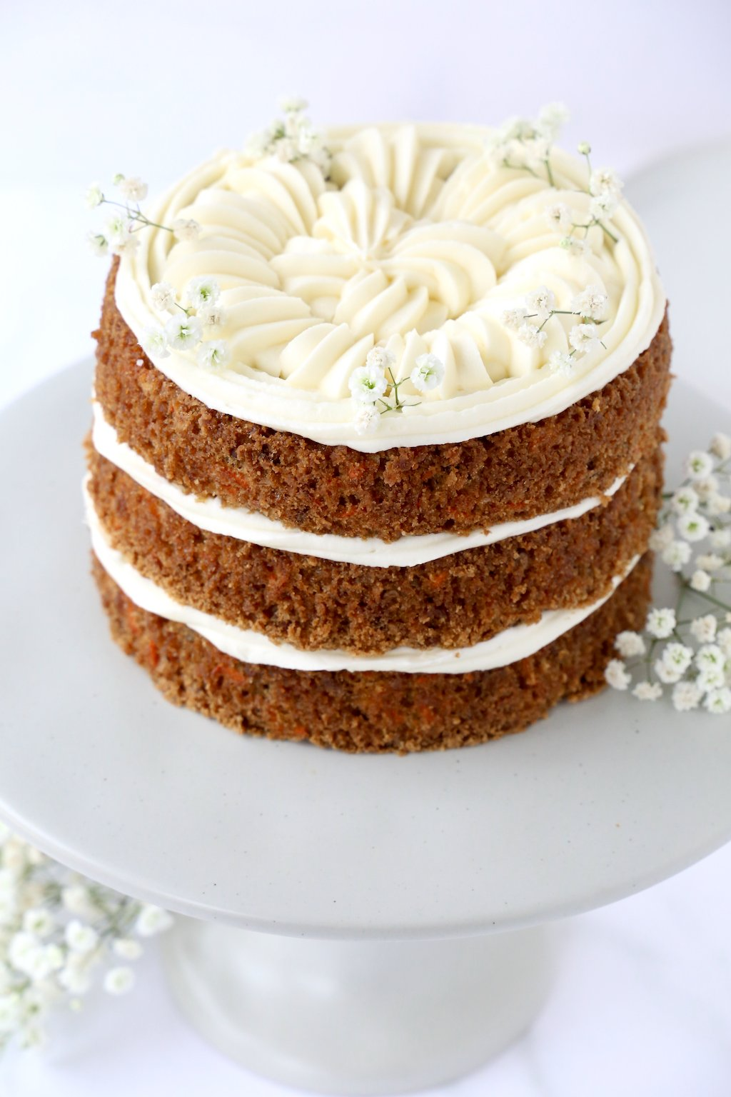 Three layers of carrot cake and cream cheese frosting on a gray cake stand