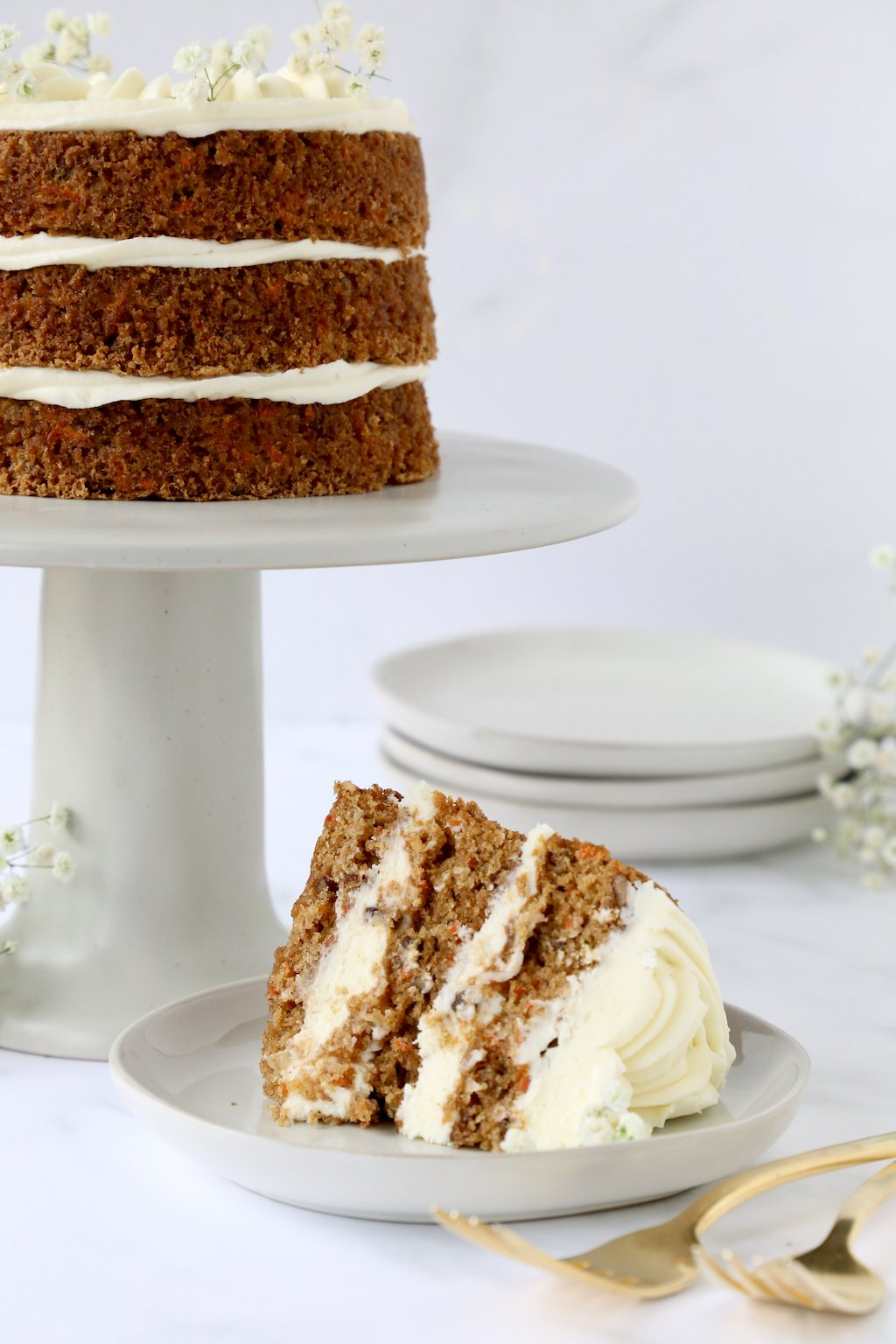 Three layers of carrot cake on a cake stand with a slice of carrot cake in front of it