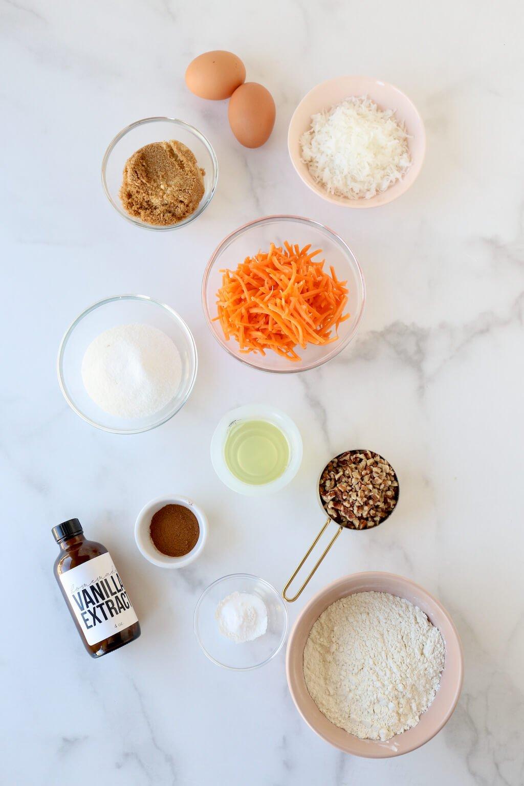 small bowls of flour, sugar, baking powder, baking soda, pecans, coconut and carrot