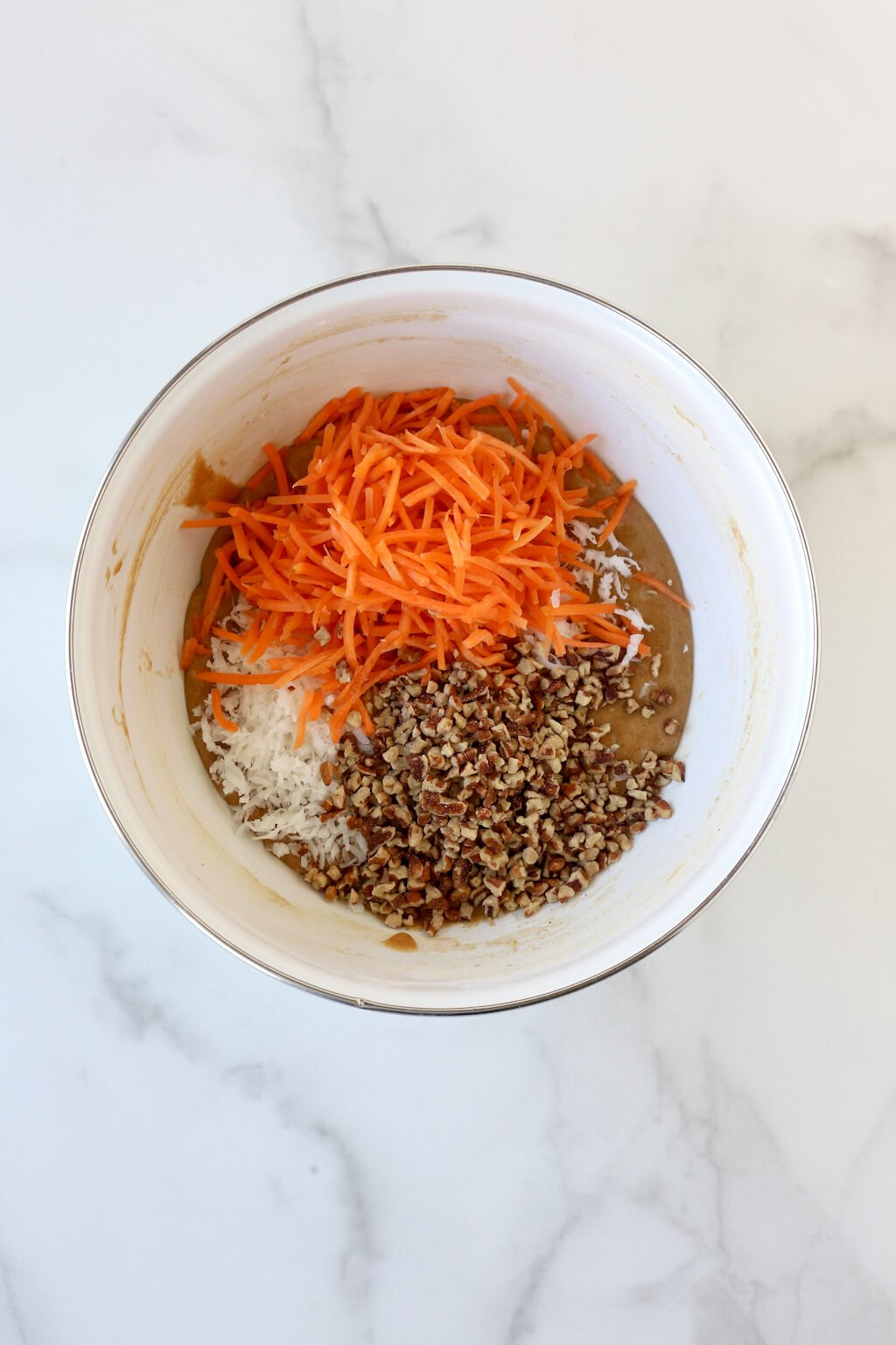 a bowl of cake batter topped with shredded carrots, pecans and coconut
