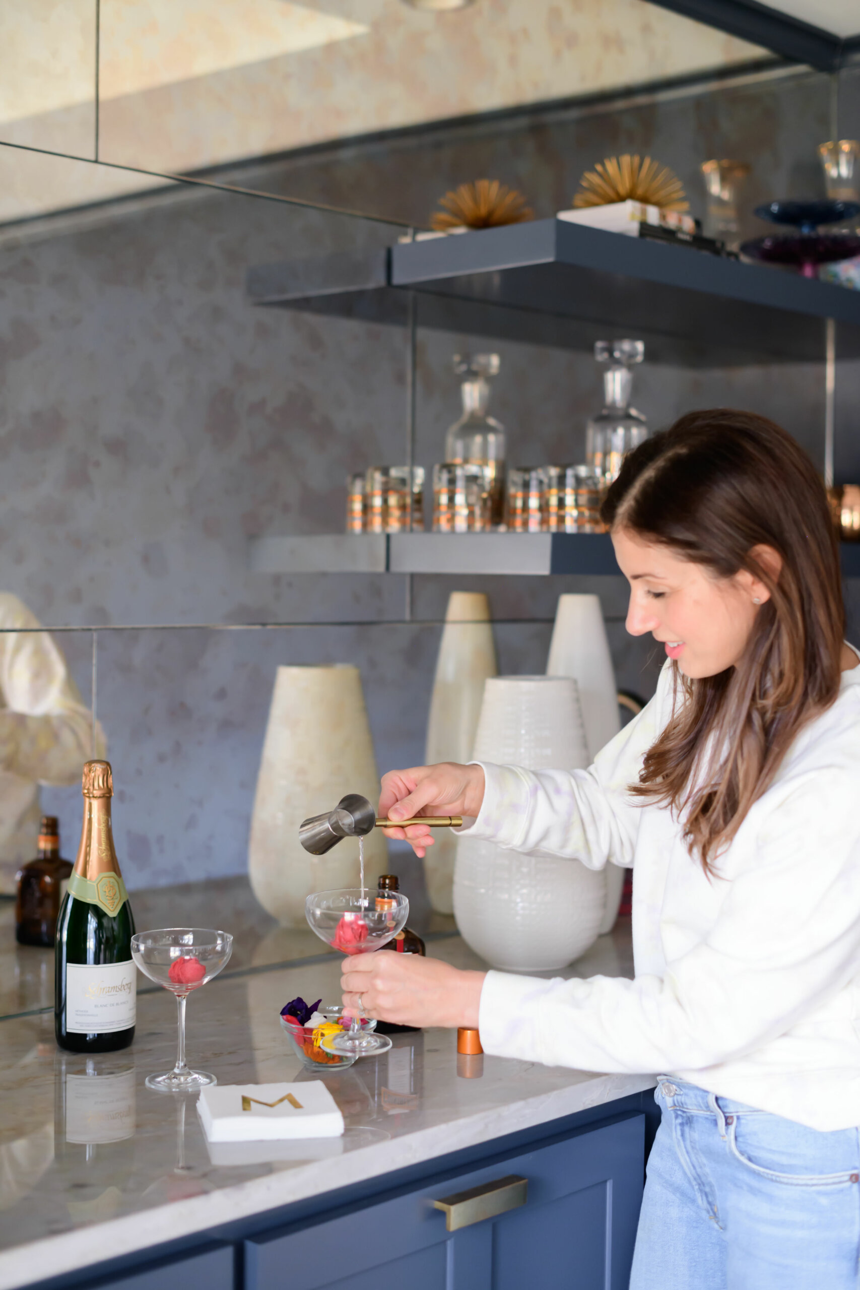 a women pouring liquor over raspberry sorbet in a wine glass