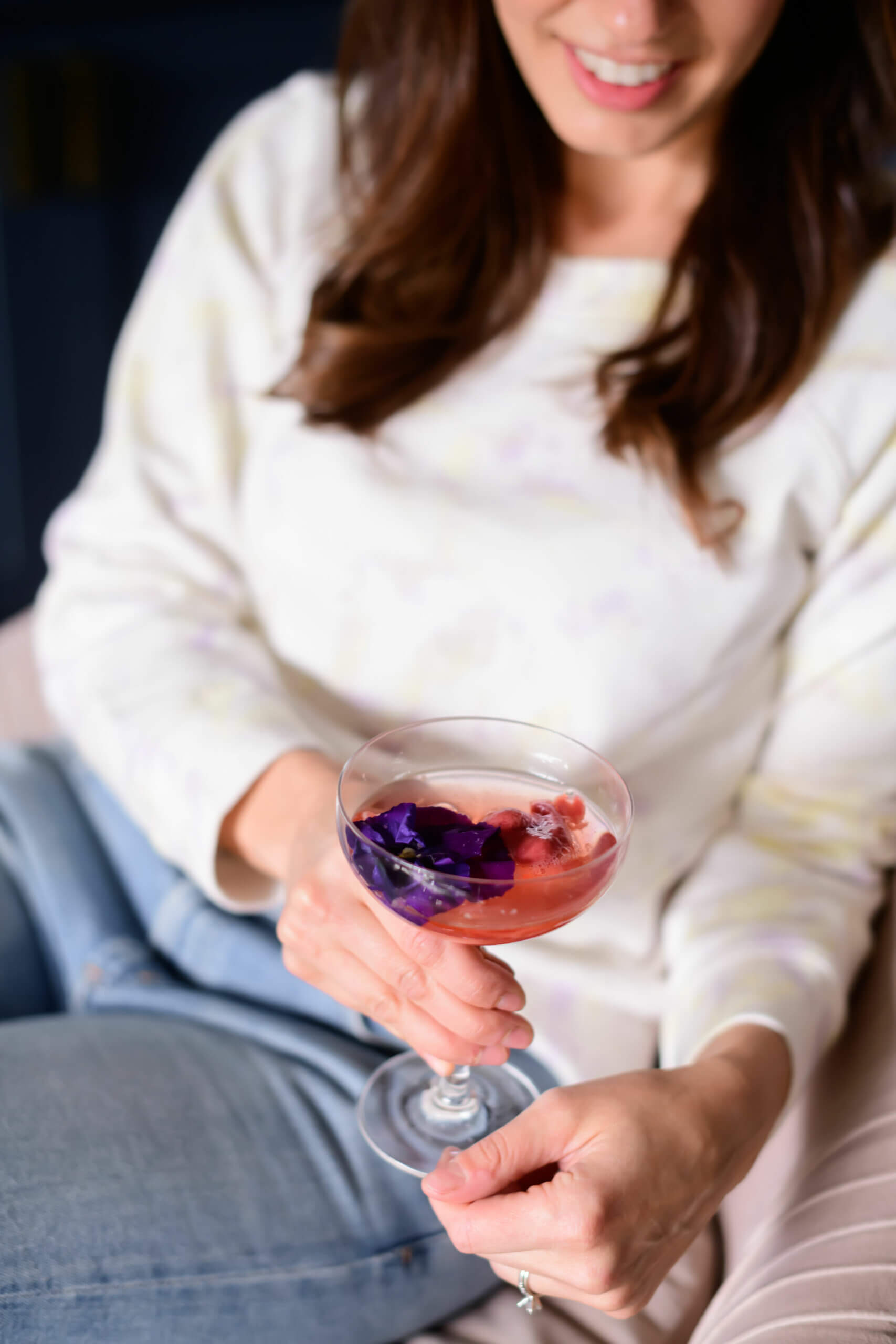 a women sitting in a chair with a glass of champagne with edible flowers