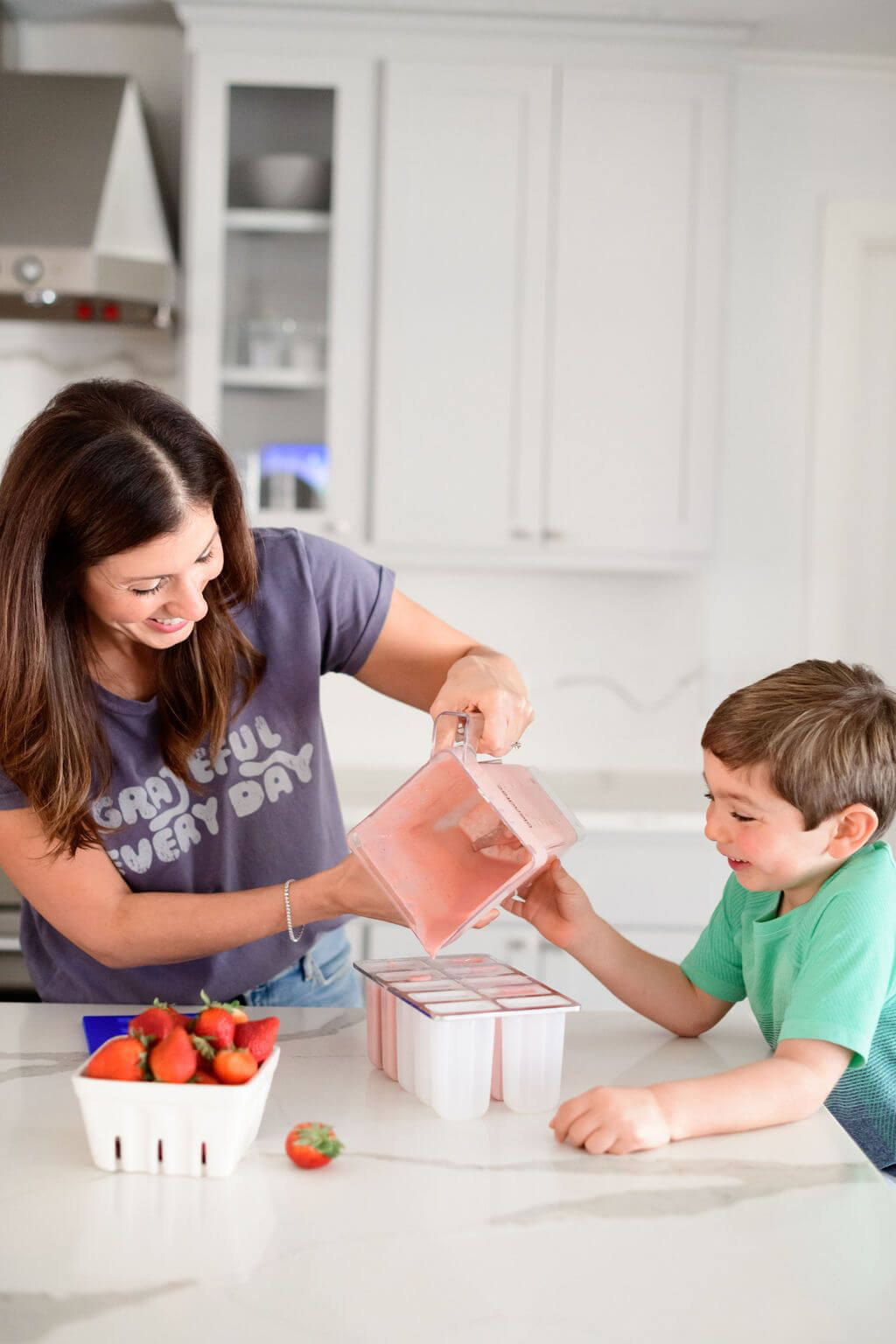 mom and son pouring the blended fruit into popsicles molds