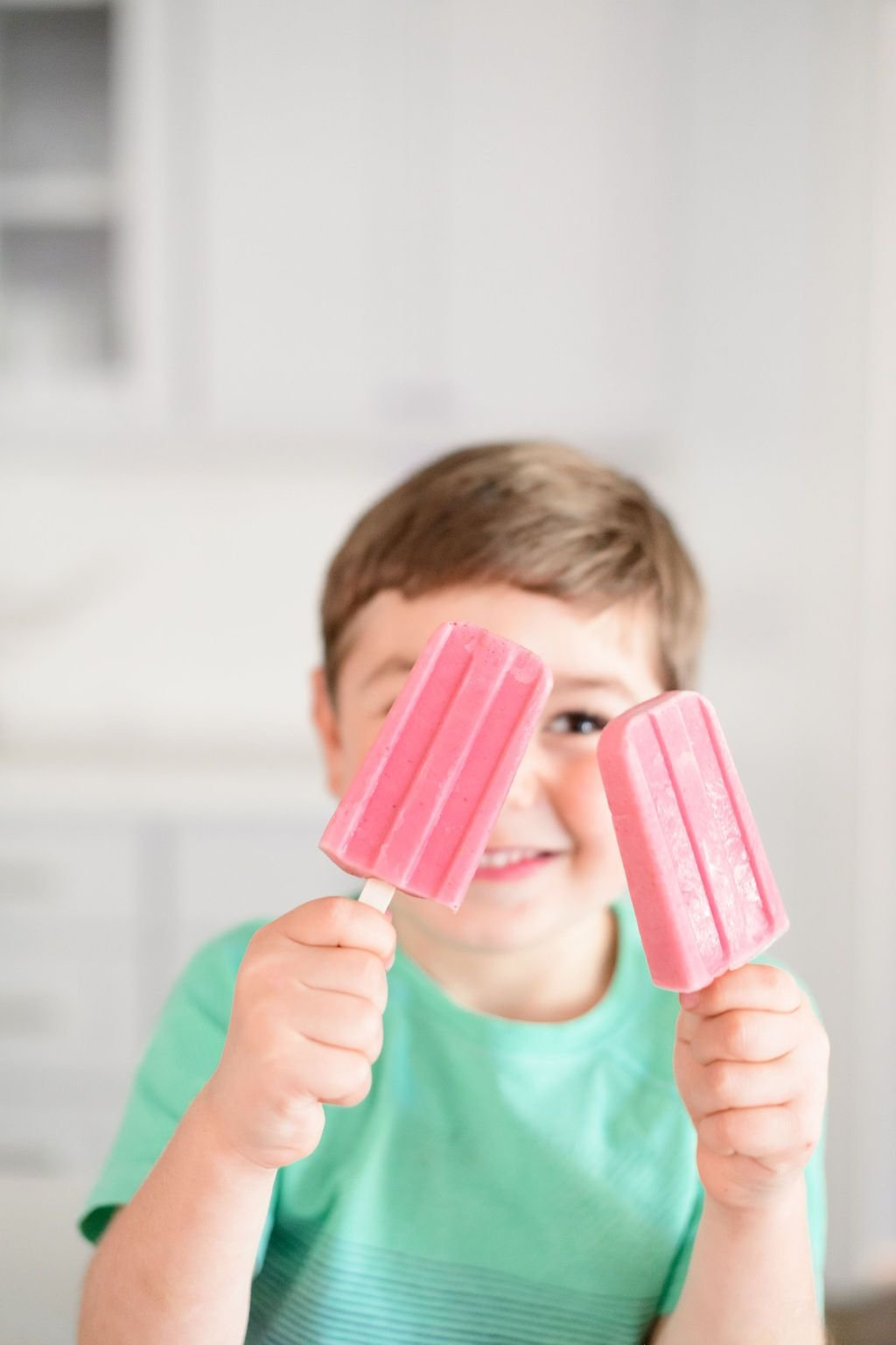 two strawberry banana popsicles held up by a little boy
