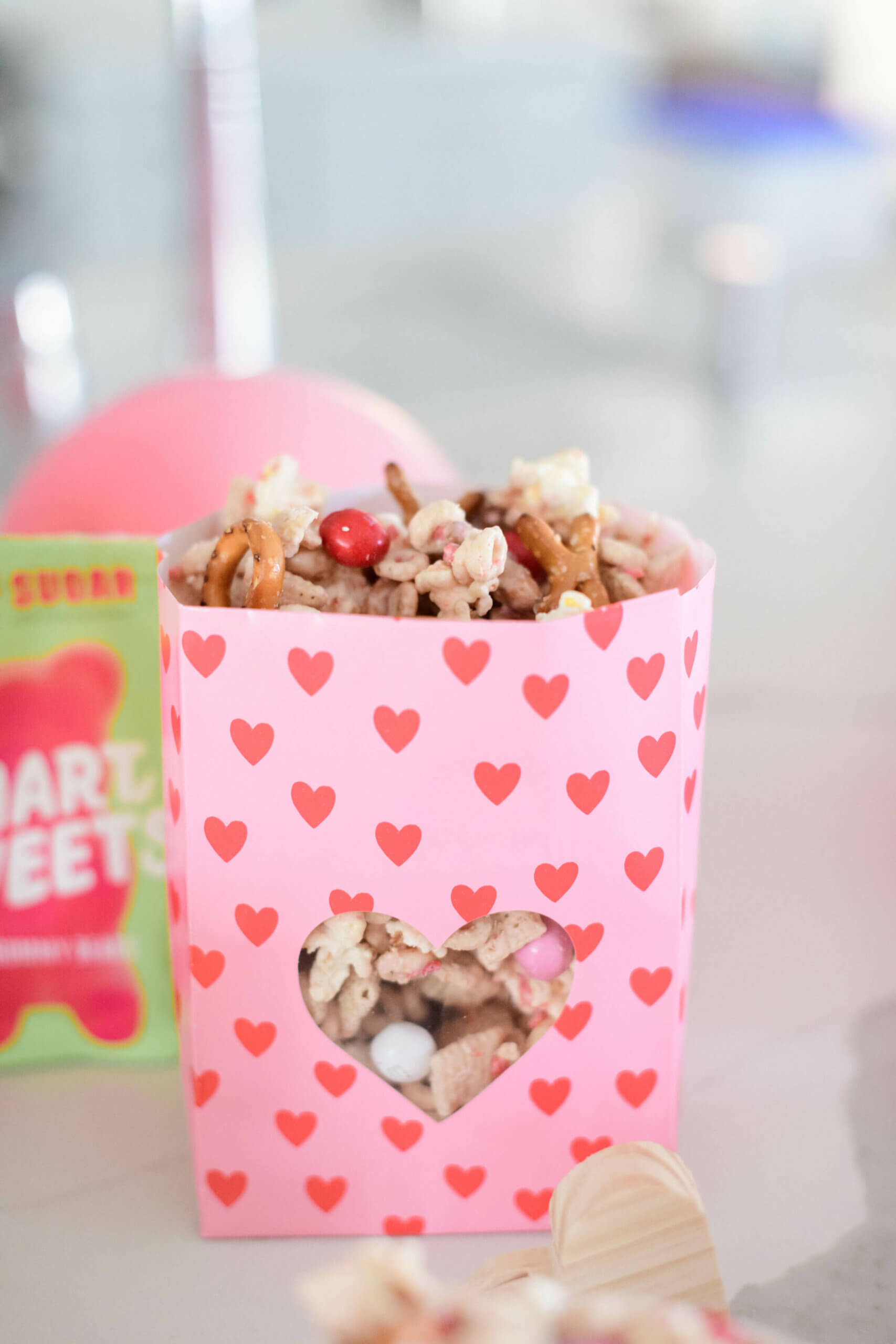a pink bag with red hearts filling with snack mix
