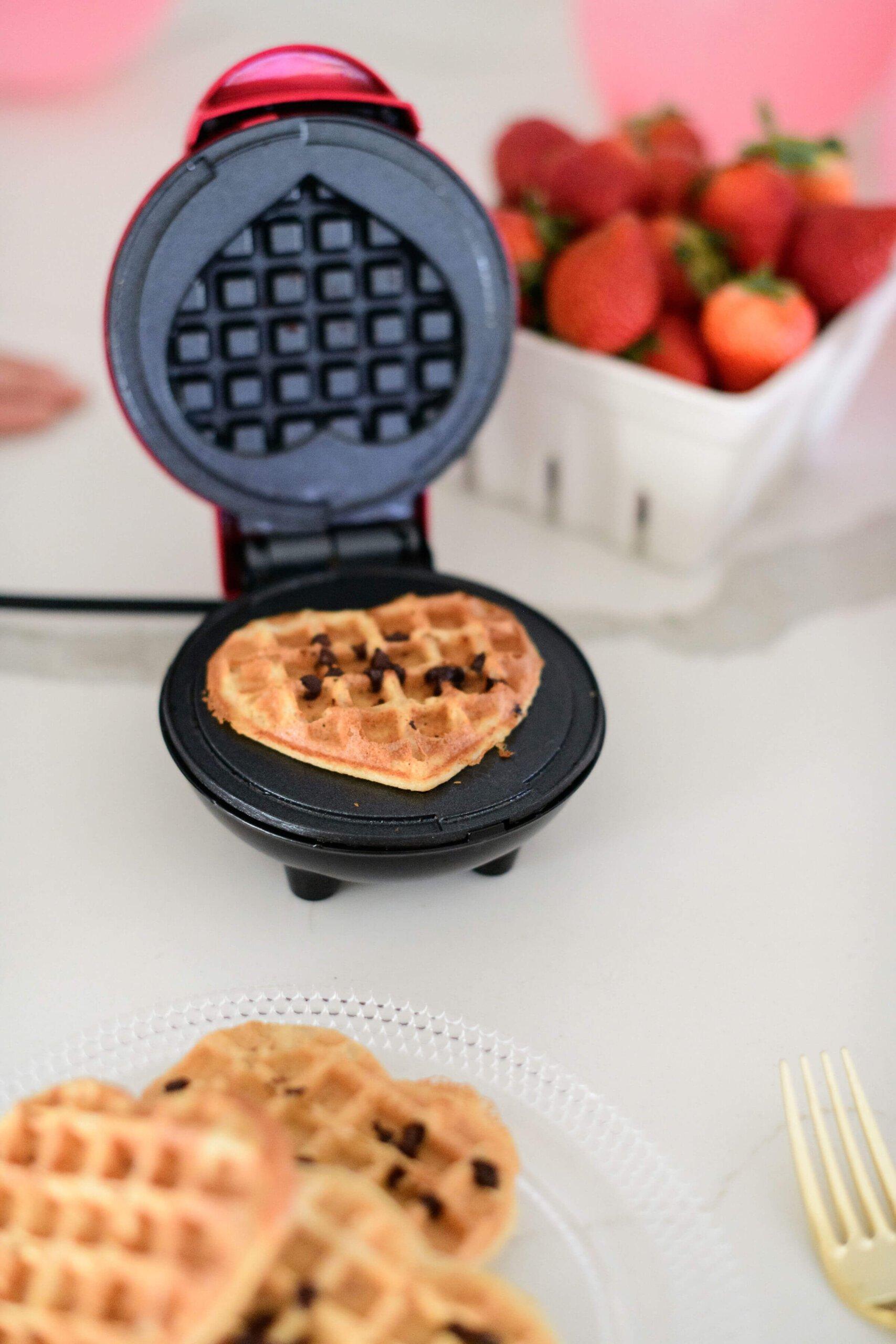 a waffle maker opened with a chocolate chip waffle inside