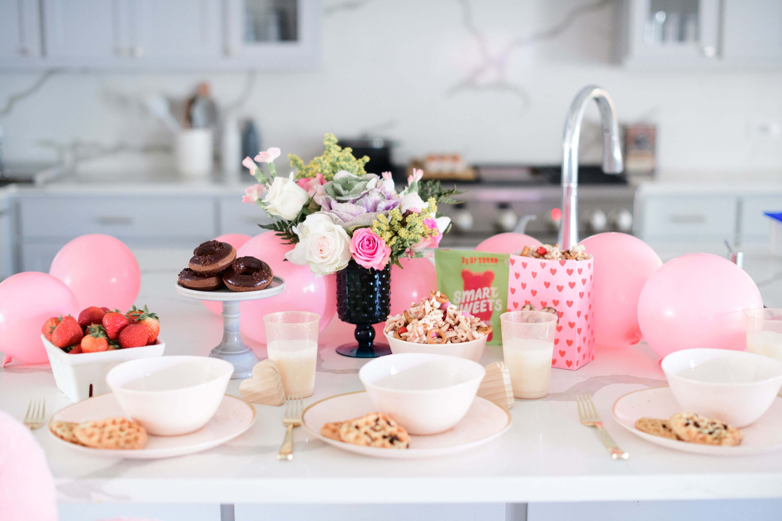a tablescape of valentine's decorations, flowers and food