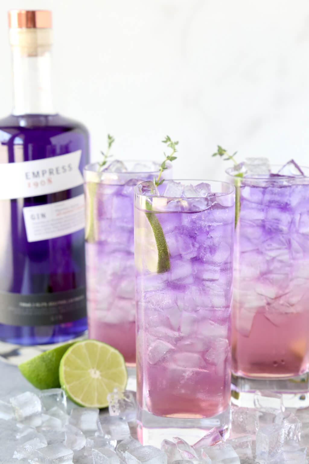 three glasses filled with ice and a purple and pink drink next to a blue bottle of gin