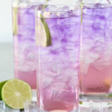 three glasses filled with ice and a purple and pink drink