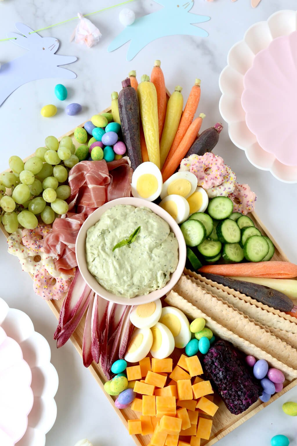 a platter of meats, cheeses, veggies and chocolate in the center of easter decorations